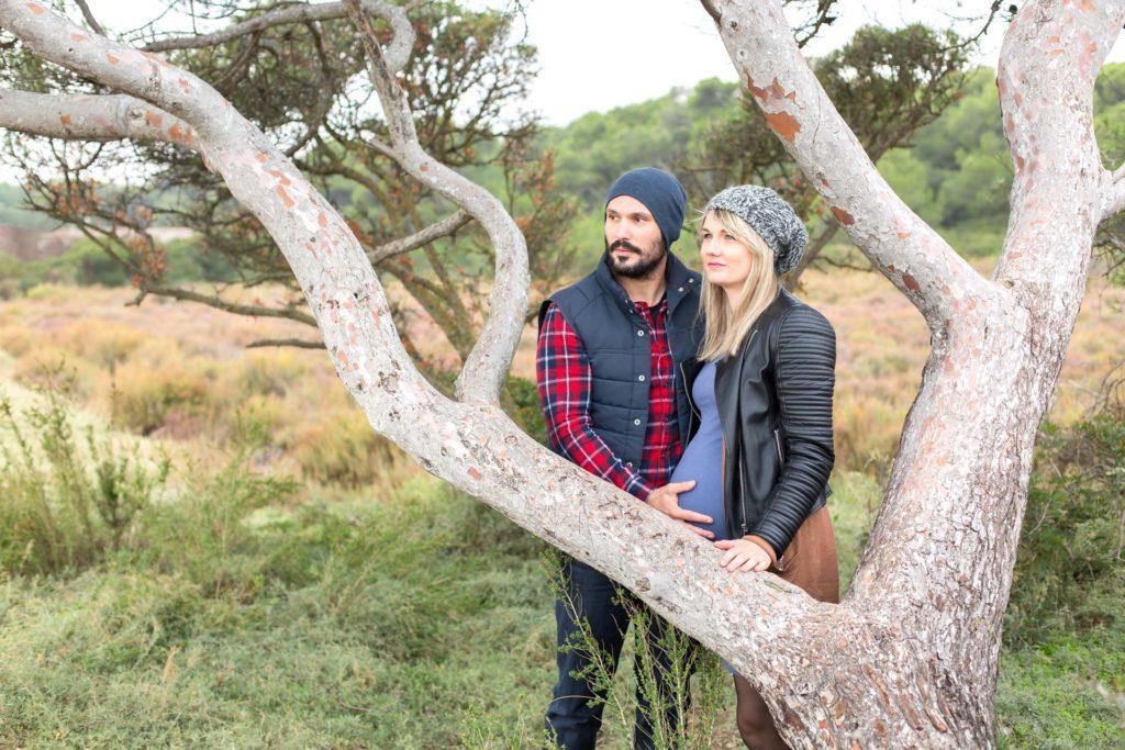 Futurs parents qui posent près d'un arbre