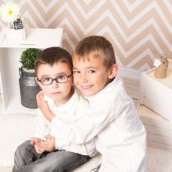 Deux garçons dans un décor avec fond à chevron beige et blanc