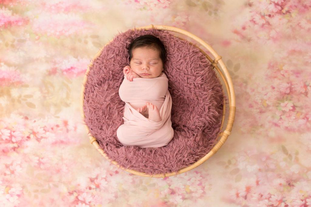 Bébé dans un panier en osier sur fond fleuri
