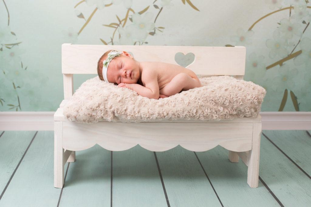Bébé fille avec un bandeau fleuri dort sur un banc en bois