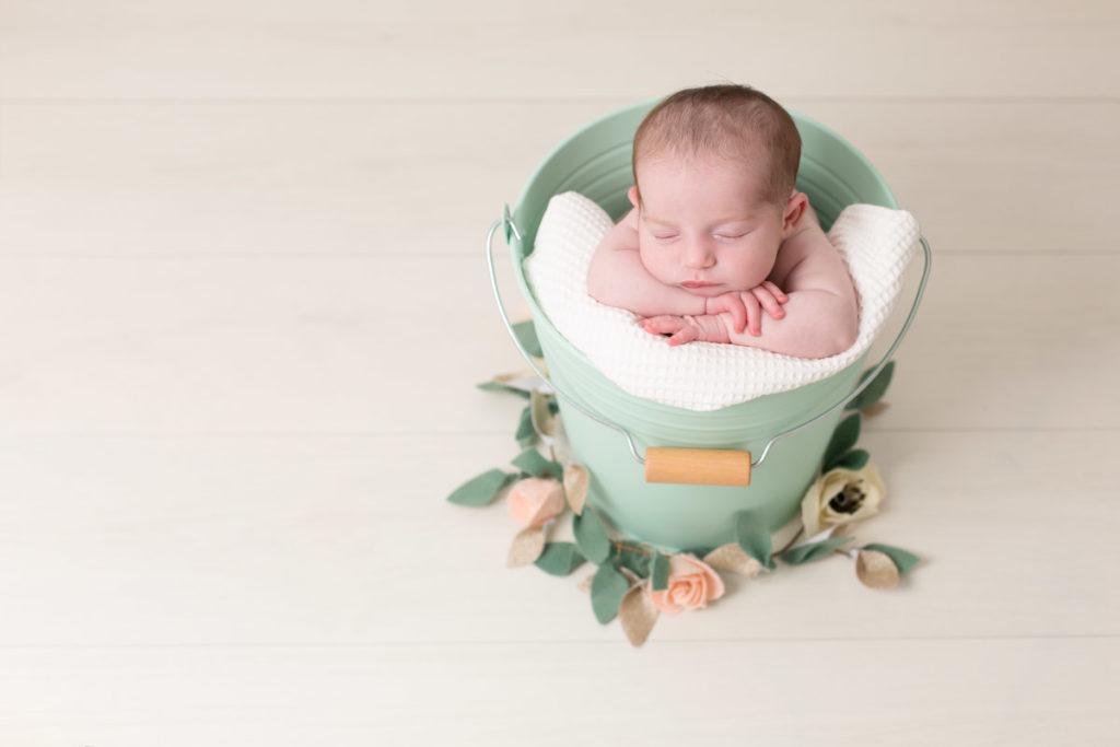 Bébé fille dans un seau vert entouré d'une guirlande de fleurs