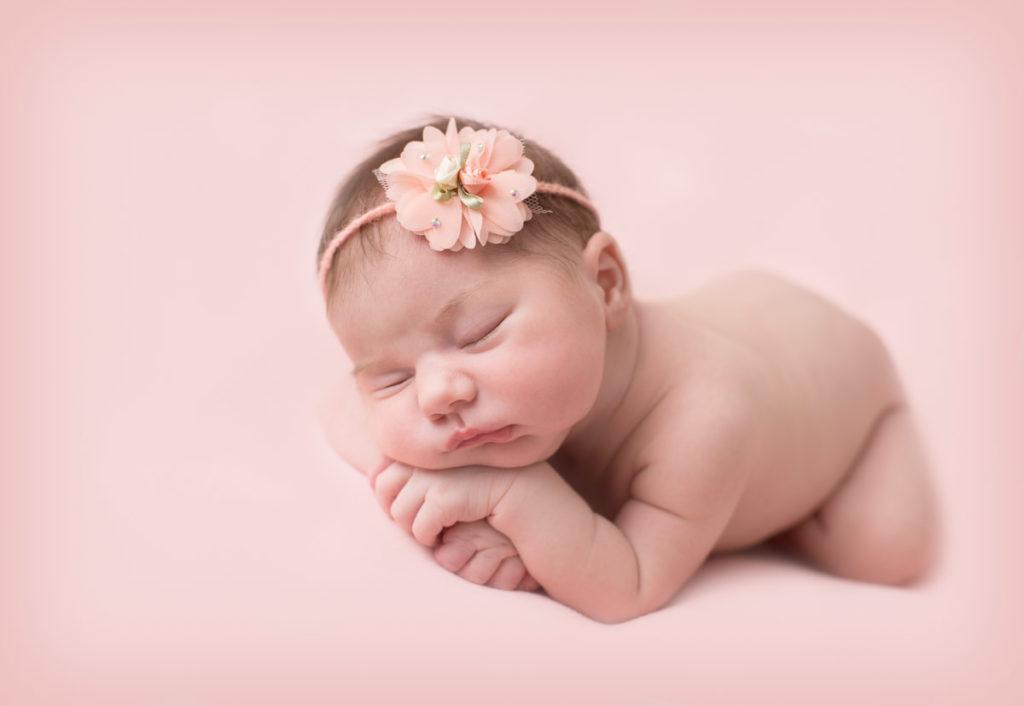 Nouveau-né avec bandeau à fleur sur fond rose